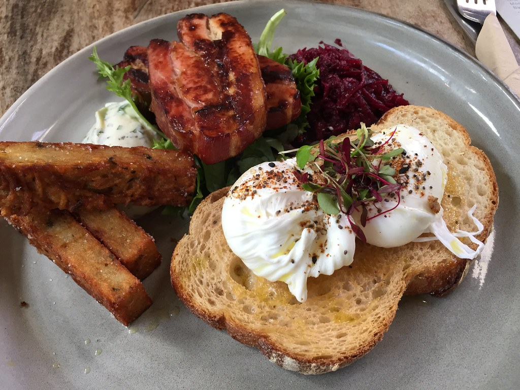 breakfast of thick cut bacon, sourdough, poached eggs, hash browns and beetroot relish at coffee collective