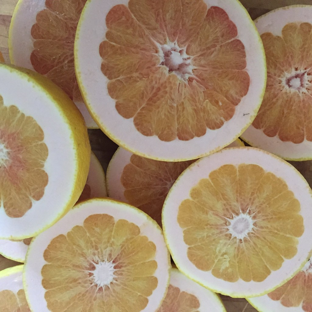 a stack f pink grapefruit, sliced in half to revel the pinky-orange flesh