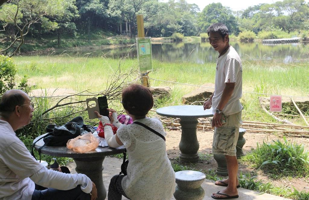 廖元興(右)和遊客解說夢湖的生態。攝影/楊孟軒。