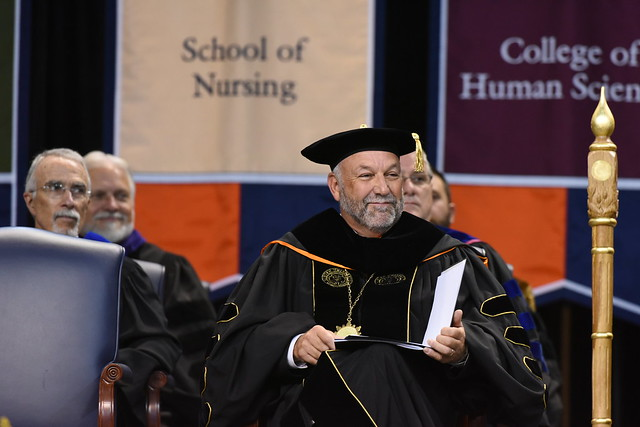 Auburn University President Steven Leath sits on stage during graduation.
