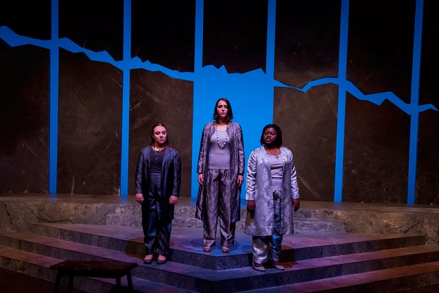 Three women stand on stage during the Auburn University Theatre's production of Antigone.