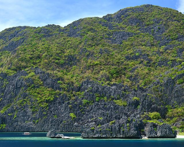 Bangka navegando por las aguas de Filipinas entre arrecifes de coral