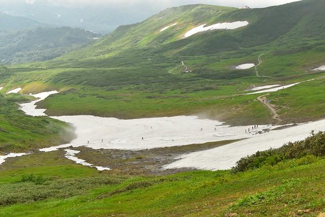 月山 設計を滑るスキーヤーと大湿原