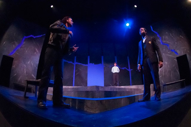 Two men face each other on stage while a third stands behind in the distance, as a blue light shines on the scene during the production of Antigone.