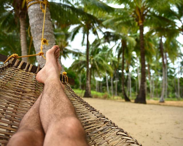 Tumbado en una hamaca filipina bajo la sombra de unos cocoteros