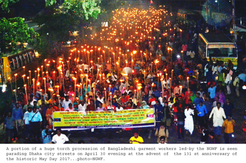 NGWF members march for May Day 2017 in Dhaka, Bangladesh. It is nighttime and many hold candles.
