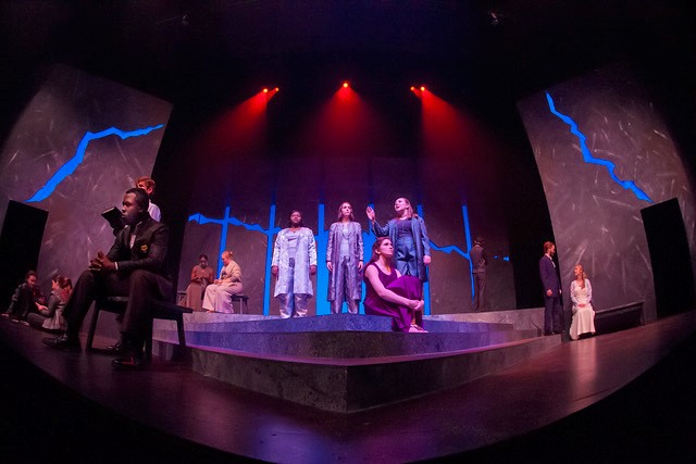 People sit and stand on stage during the Auburn University Theatre's production of Antigone.