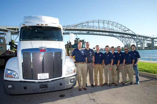 A semi-truck with eight men standing next to the cab. A bridge is in the background.