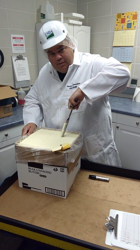 "Matthew Siedschlaw, a USDA butter grader, using a ""trier"" to remove a sample of butter"