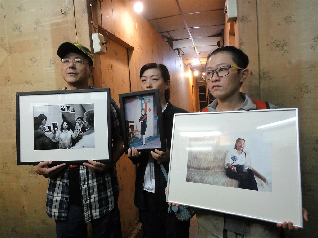 日日春聲援者手拿原掛於文萌樓牆上的逝世公娼官秀琴、麗君、白蘭的照片。(攝影:張智琦)