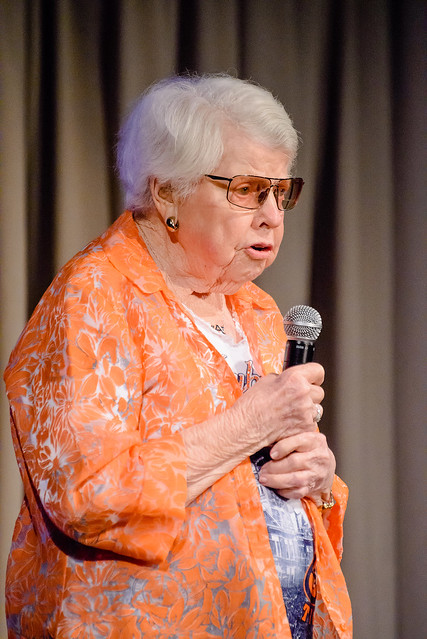 Helen Leslie speaks into a microphone on stage.