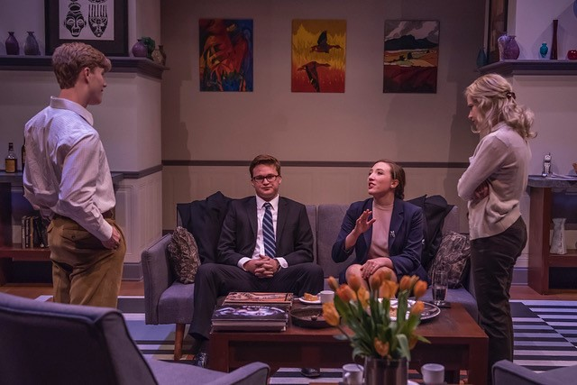 """Two cast members are sitting on a couch and two cast members are standing in the room during Auburn University's Department of Theatre's production of """"God of Carnage."""""""