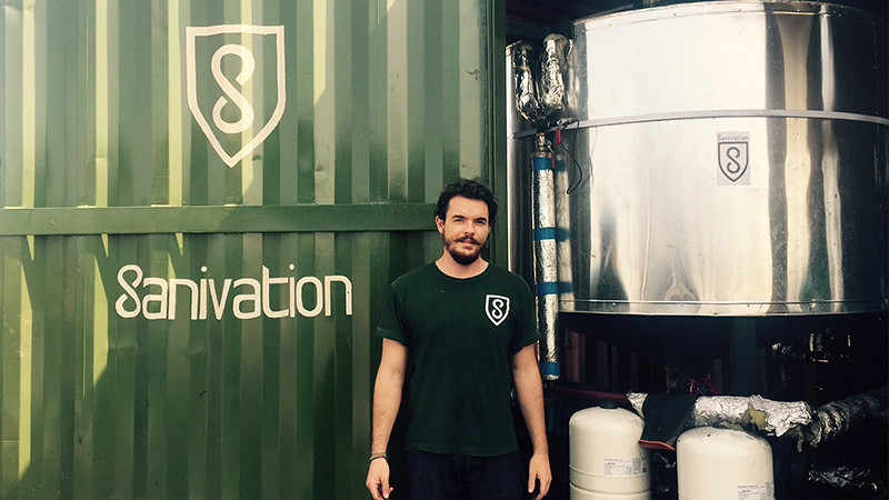 Jack stands in front of a sign for Sanivation painted on a green shipping container.