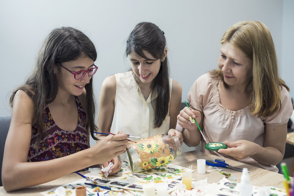 youth worker with two teenagers doing an arts and crafts workshop