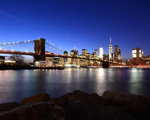 Puente de Brooklyn al anochecer por donde fuimos en barco frente a las luces del skyline de Manhattan