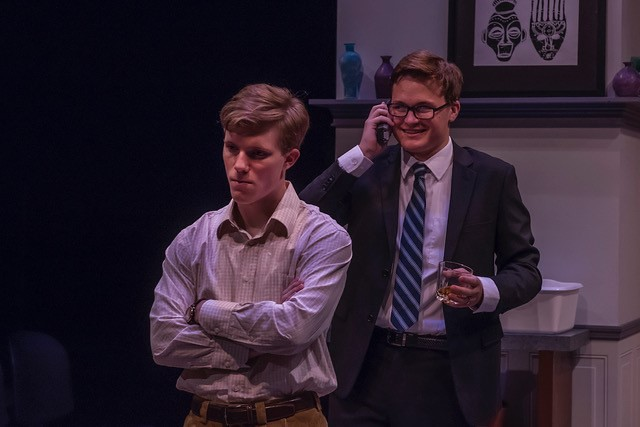 """A male cast member is on the phone holding a drink while smiling behind another male cast member during Auburn University's Department of Theatre's production of """"God of Carnage."""""""
