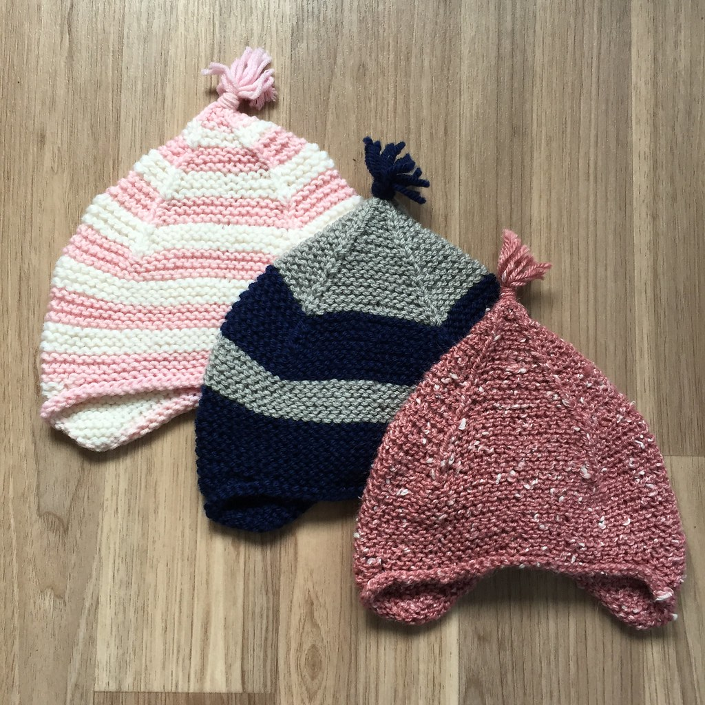 a collection of 'kid' sized garter ear flap hats in different yarns