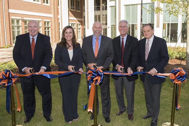 Five people stand in front of a new building, cutting a ribbon.