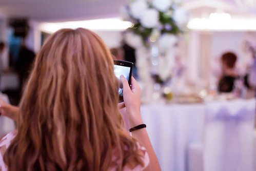Girl taking photo with a smartphone at a wedding | by wuestenigel