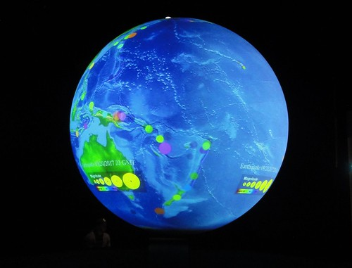 Image shows a hemisphere of Earth projected onto a sphere suspended from the museum ceiling. Australia is shown in green towards the left of the hemisphere; circles representing earthquakes outline its plate.