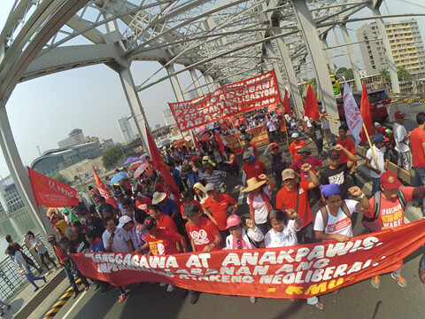 Protesters carry a sign over a bridge, blocking it for May Day and wearing red