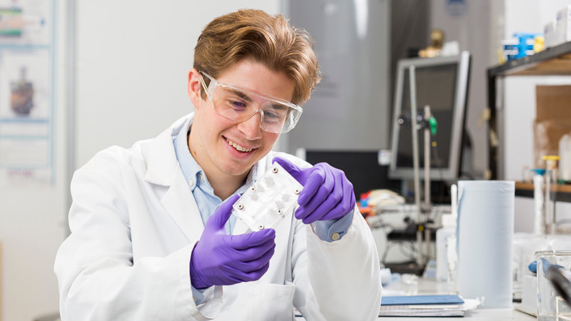 Luke Wilson examines a biofuel cell in one of our chemical engineering laboratories