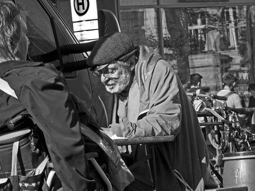 Älterer Mann sitzt an einem Imbiss in der Sonne