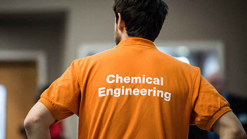 Student in a chemical engineering helper t-shirt looks away from camera