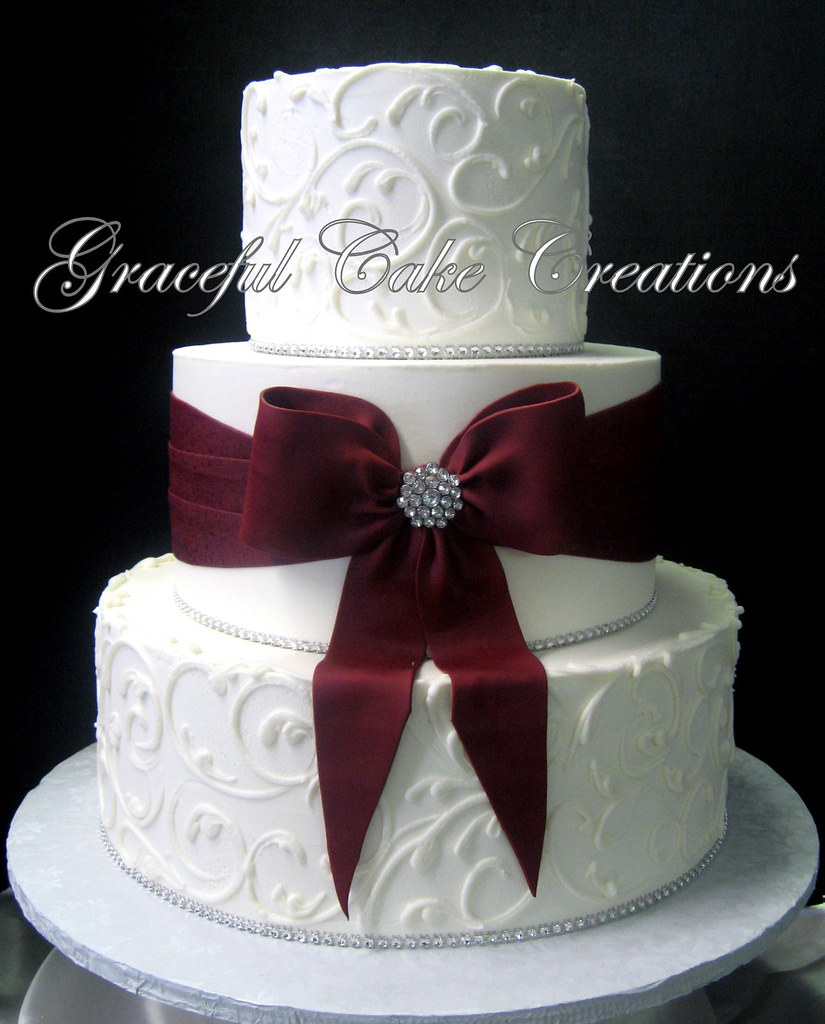 Elegant White Butter Cream Wedding Cake With A Burgundy Sa