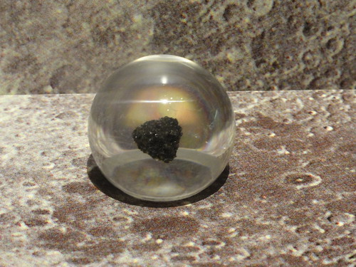 Image shows a triangular bit of rough black basalt suspended in a clear Lucite sphere. It's resting on a background made from a photo of the moon.