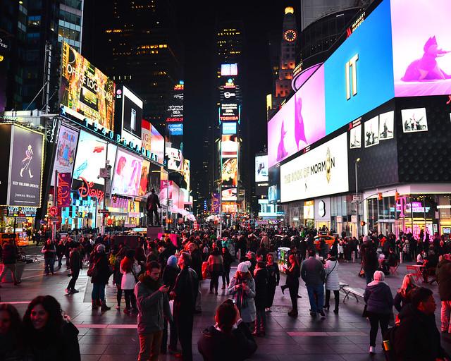 Times Square iluminado en la noche repleto de colores con luces de neón