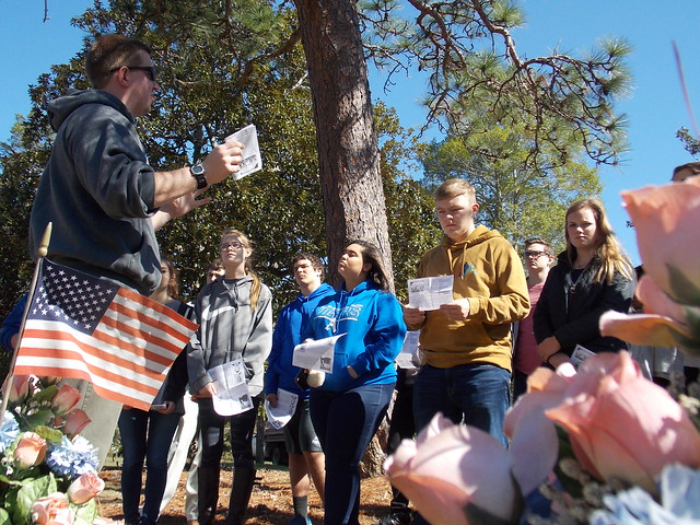 Three-time Auburn graduate Blake Busbin stands with a group of students outside in a cemetery as they gather information for an oral history project.