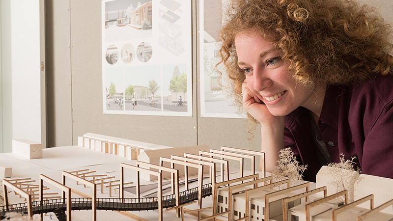 Gemma smiles as she looks at her model for a railway station.