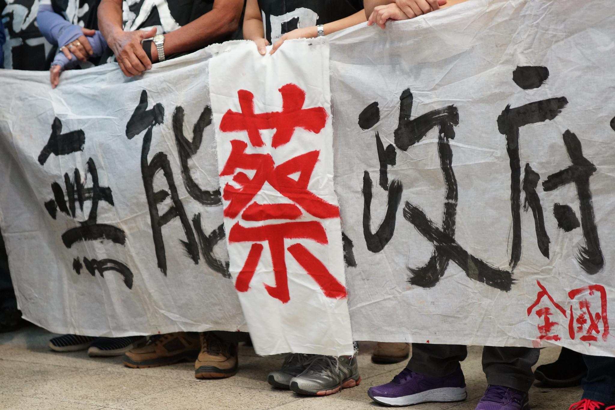 """全关连现场重新拉起当年抗争布条,并把""""马政府""""改为""""蔡政府"""",政权虽更迭,但对待工人运动的态度却很一致。(摄影:王颢中)"""