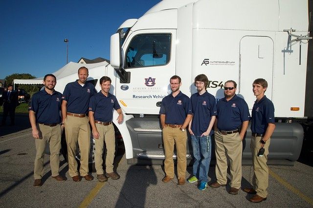 Seven men stand next to the cab of a semi-truck.