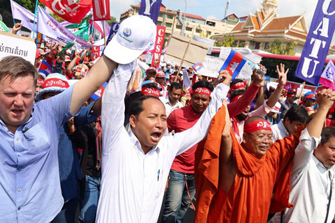 Leaders of C.CAWDU march for May Day 2017, holding their hands up together in unity, holding a Cambodian flag