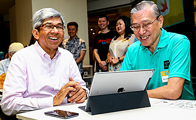 Dr Yaacob Ibrahim with 71-year-old Foo Chee Meng (right), a Senior Inforcomm Wellness Ambassador (SIWA) from IMDA, who has been trained to learn coding prior to the event to enable them to facilitate the Hour of Code for more seniors. Photo: NLB.