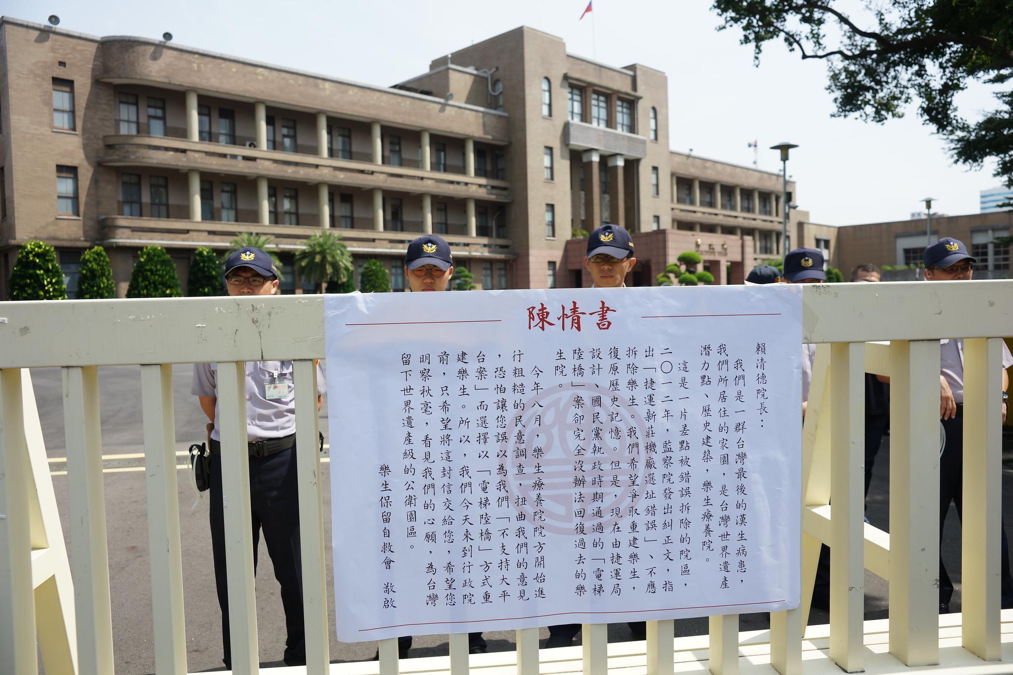 自救會將陳情書張貼在行政院大門前。(攝影:王顥中)