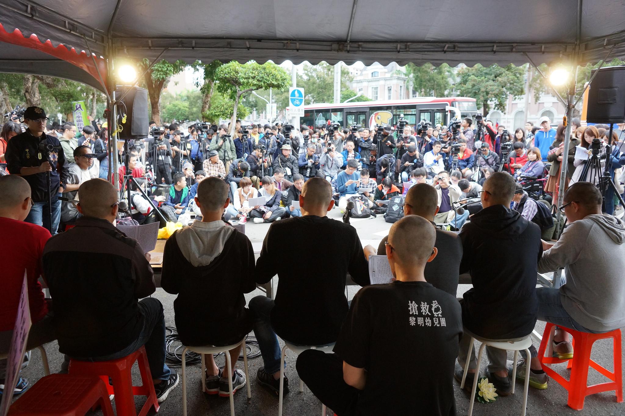參與民眾也端坐台前,雙手合十共同誦經。(攝影:王顥中)