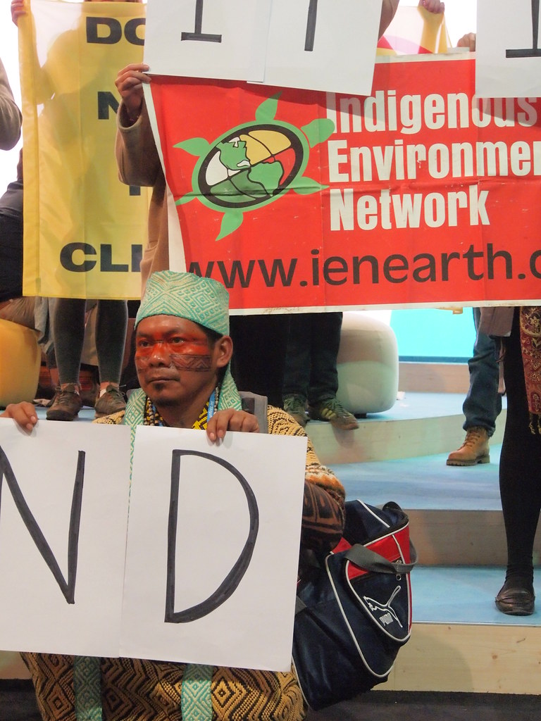 來自巴西阿克里 (Acre) 亞馬遜叢林的 Huni Kui 族領袖 Ninawa Nuneshuni Kui。為了參加波昂氣候峰會,他花了一天時間坐船出叢林、一天時間搭車到機場和一天的時間飛行。大老遠奔波,只為了將化石燃料文明入侵故鄉、分化族人的故事帶到聯合國現場。