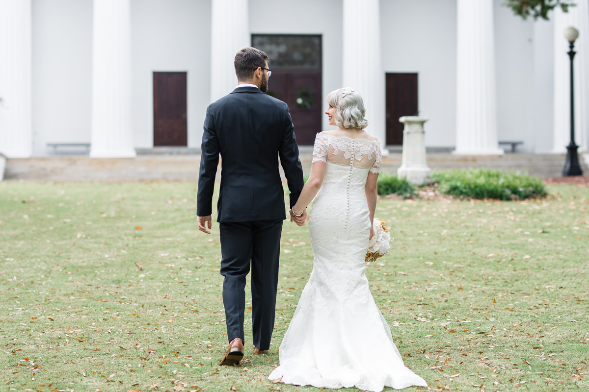 Photo by Garter and Whiskey - Bride and Groom Walking Away Lace Dress Navy Suit