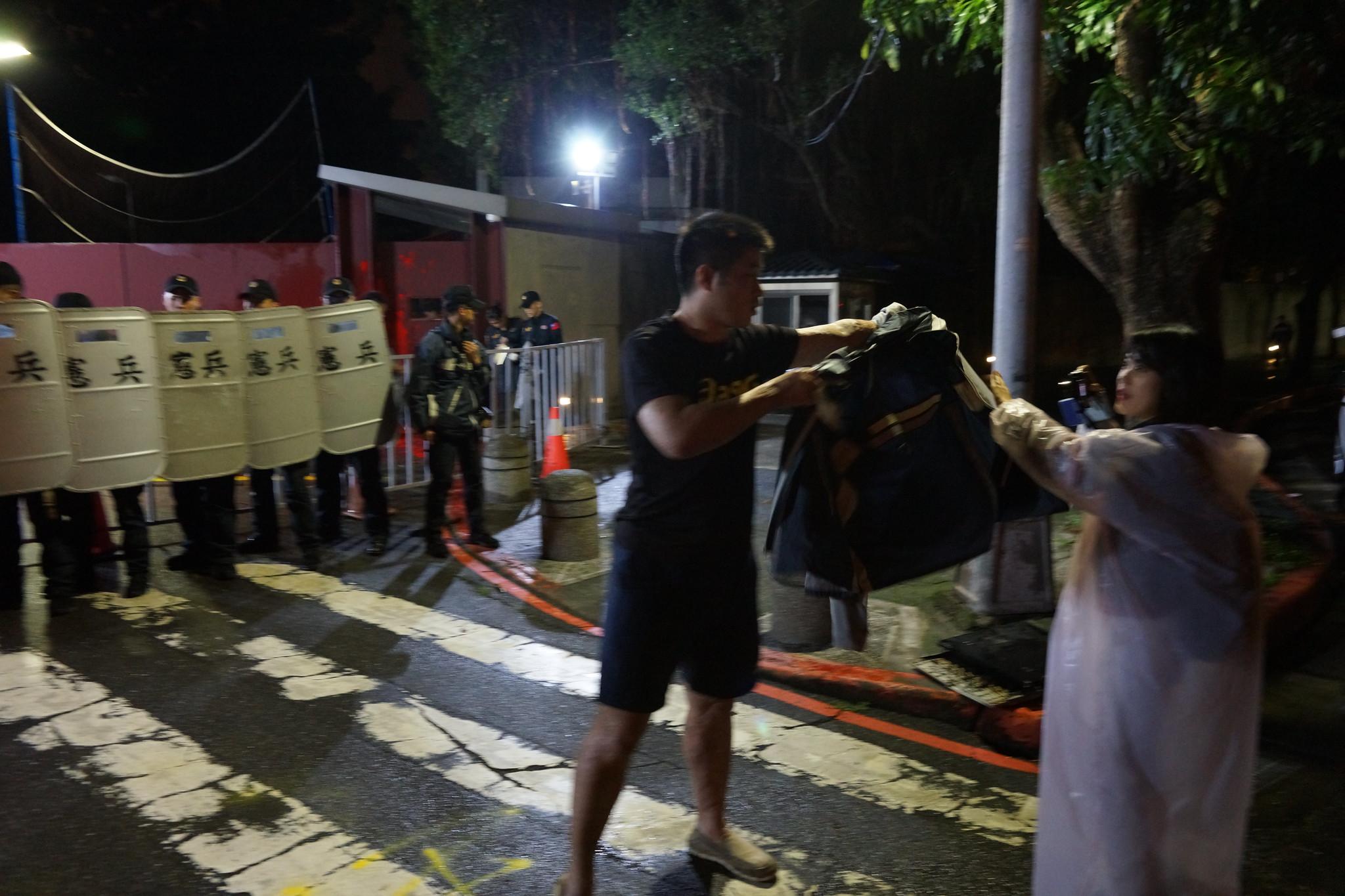 昨日才有《風傳媒》記者在採訪過程中遭脫離引發爭議,今日行動現場,憲警用外套阻擋拍攝,圖為公視記者採訪受阻畫面。(攝影:王顥中)