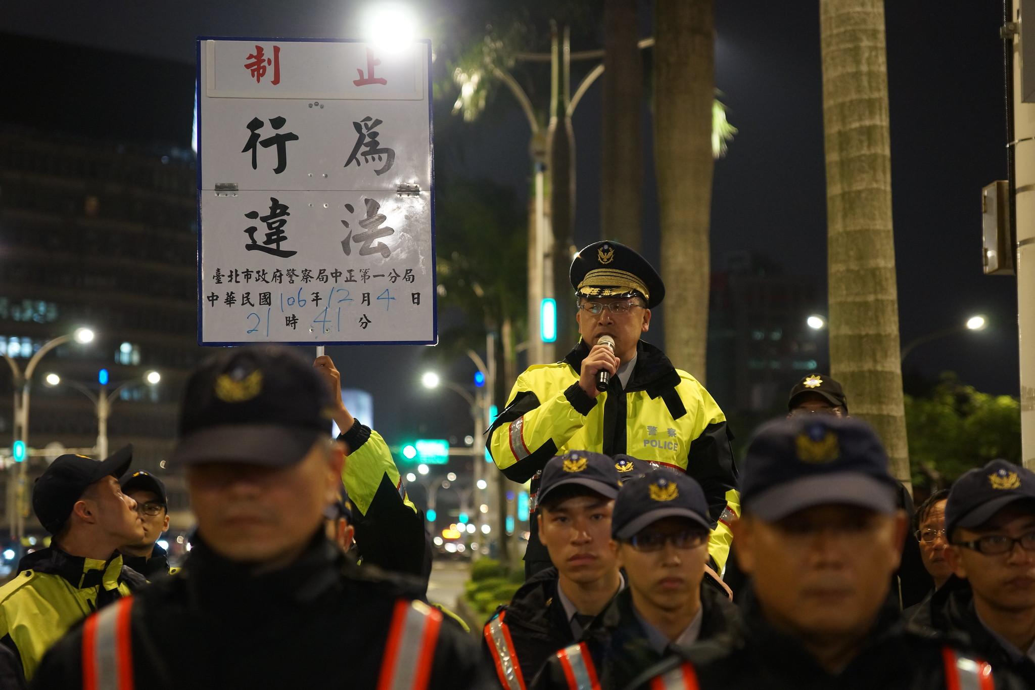 警方晚間9點41分舉牌警告,並在隨後開始抬離抗議民眾。(攝影:王顥中)