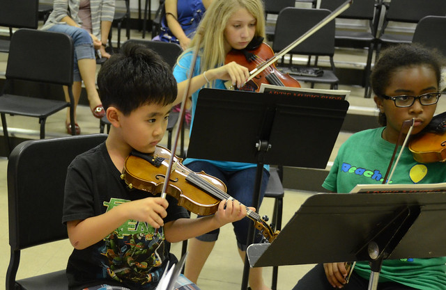 Three elementary school students play string instruments and read music from a music stand.