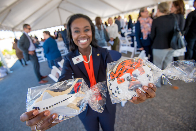 A young lady holds up a tiger face-shaped cookie and an airplane-shaped cookie.