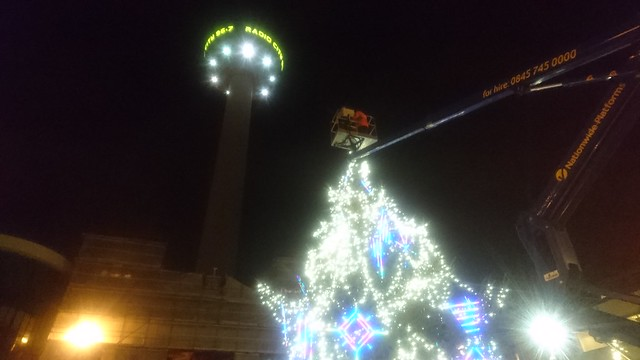 Placing the star at the top of the tree from the cherry-picker