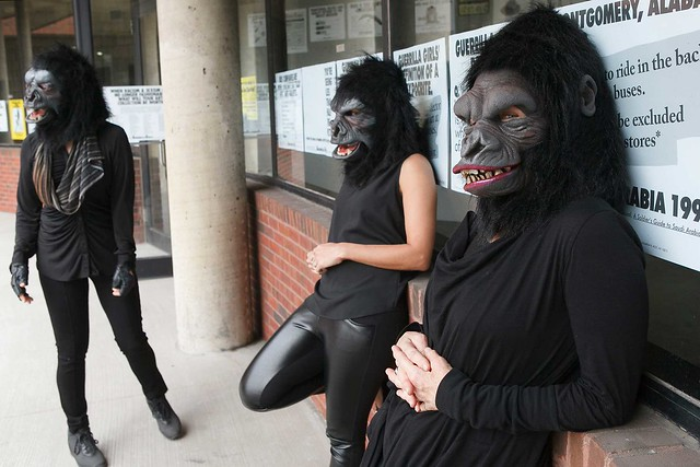 Three people stand wearing gorilla masks