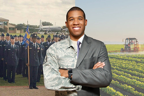 An airman with a backdrop of a group of veterans and a tractor on a farm