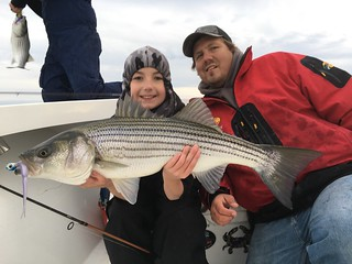 Photo of Ayden Smith proudly holding up his prized striped bass
