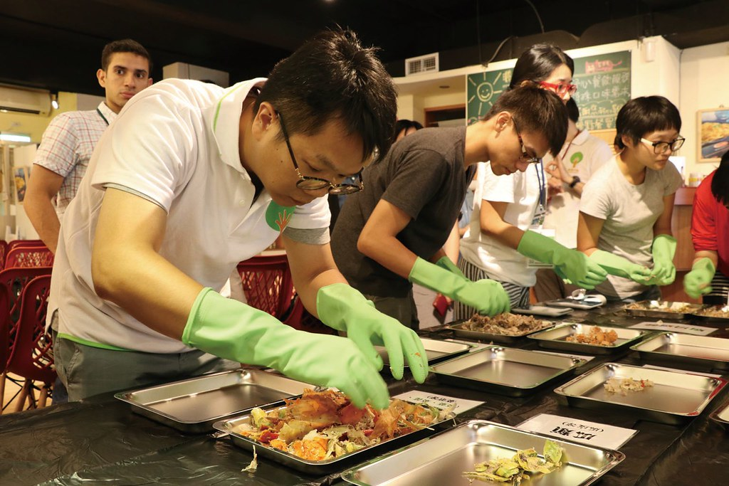 香港綠領行動成員正帶領工作坊學員仔細分類餐廳的廚餘,分類後會逐一秤重並記錄。